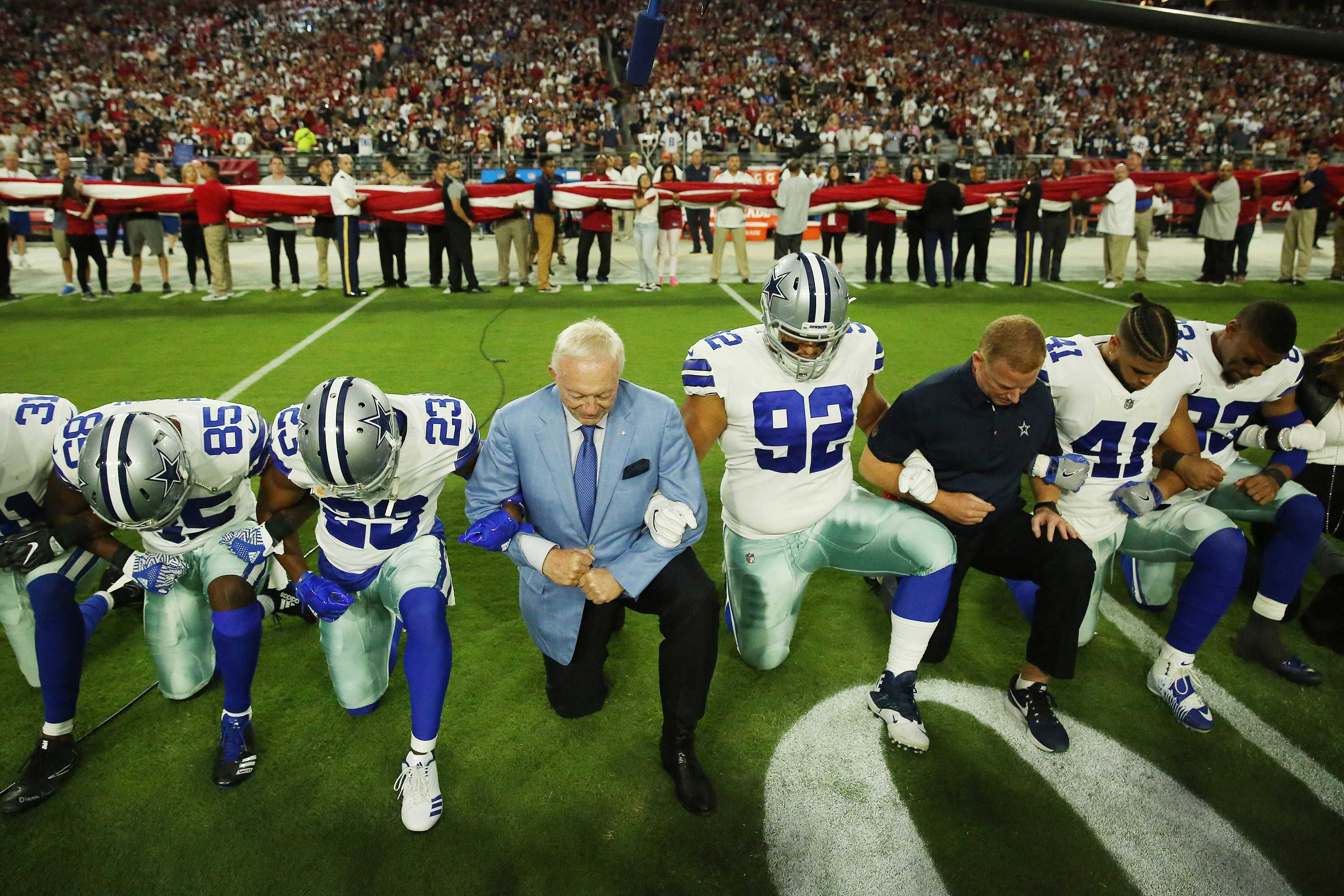Dallas Cowboys players and staff including owner Jerry Jones and head coach Jason Garrett all take a knee before the singing of the National Anthem prior to the start of a game against the Arizona Cardinals at University of Phoenix Stadium Monday, Sept. 25, 2017 in Glendale, Ariz. (Vernon Bryant/Dallas Morning News/TNS)