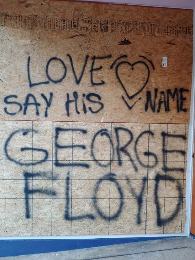 Message spray-painted on the side of a building.