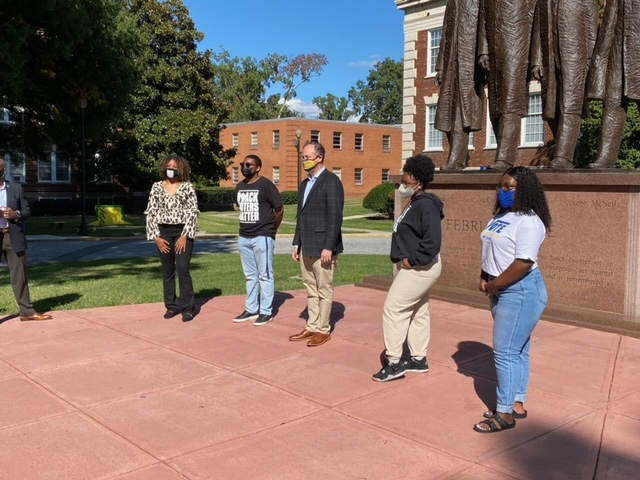 Doug Emhoff takes a photo with N.C. A&T students in front of the Greensboro Four statue.